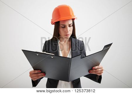 Serious woman in formal wear and hard hat familiarize with the materials in big black folder