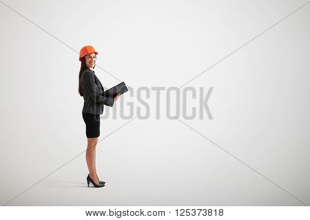 Standing woman in formal wear and construction helmet holding materials in black folder, side view
