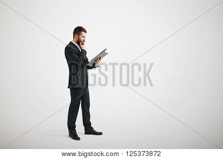 Thoughtful man in formal wear familiarize with materials in the folder