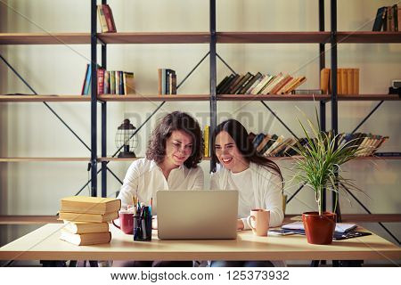 Two women sitting at the table and working at a laptop, bookshelves on a background
