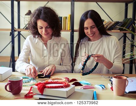 Two women with handmade bijouterie. A lot of things on the table near