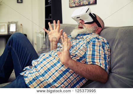 Senior Caucasian man afraid of what he sees using white virtual reality headset glasses