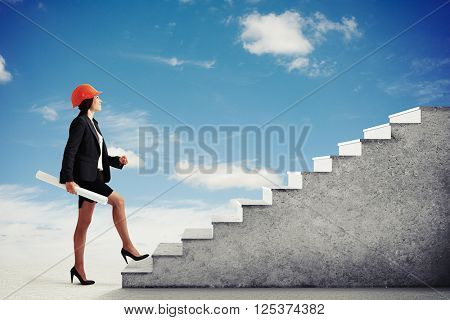 Girl in formal wear and hard hat climb the concrete stairs in a light cloudy sky, side view