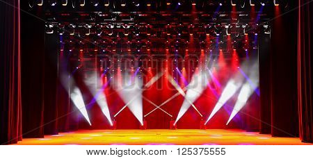 Illuminated empty concert stage with red light and stage fog