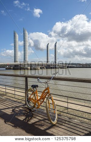 Bordeaux, France - March 27, 2016. Orange bike in front of Pont Jacques Chaban-Delmas in Bordeaux. Aquitaine. France.