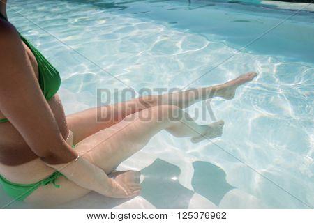 Woman enjoying sunbath in swimming pool on a sunny day