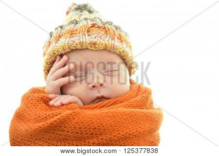 Portrait of a cute sleeping baby in orange plaid and hat over white background