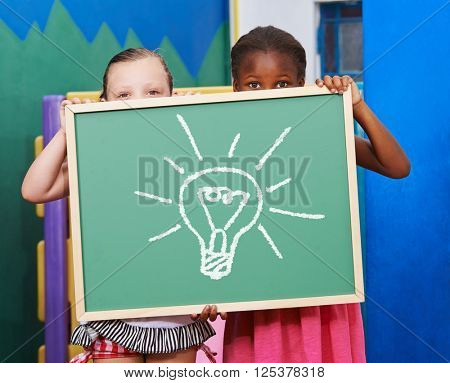 Two children holding a chalkboard with a lightbulb drawn on it