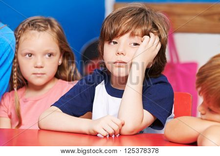 Child is bored and sitting at table in kindergarten