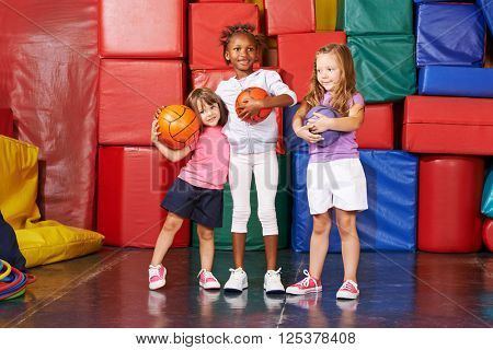 Three happy girls standing with balls in a gym of a preschool
