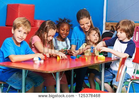 Children an teacher playing with building blocks together in preschool