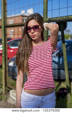 Beautiful young woman, outdoors, resting in a bright red T-shirt, fashion style, adjusting happy brunette hair, in red sunglasses fence