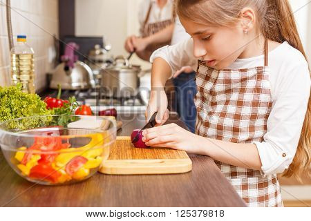 Small Girl Cutting Onion On The Kitchen Counter
