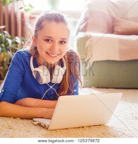 Young Teenage Girl Has Fun Using Laptop At Home