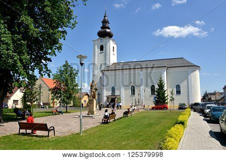 Predmier Slovakia - May 26 2012: Roman Catholic Church of saint Gall in summer and some people arround