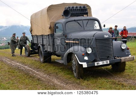 Strecno Slovakia - July 21 2012: Historic truck with two men dressed in german nazi uniforms during historical reenactment of World War 2 battle