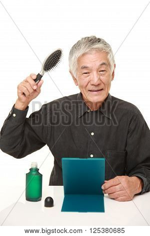portrait of senior Japanese man using hair restorer