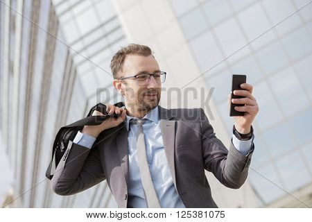 Businessman with a bag over his shoulder using smart phone in front of the blue glass business building