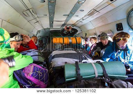 Group of Mountain Climbers Sitting Inside Helicopter with Large Heap of Luggage
