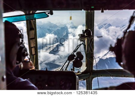 View through Helicopter Cockpit Flying at High Altitude Mountain Pass in Remote Area of Asia