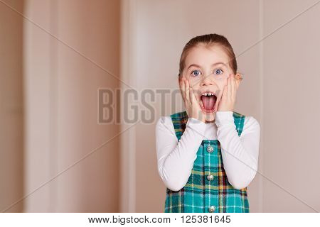 A cute little girl gasping at the camera inside white room