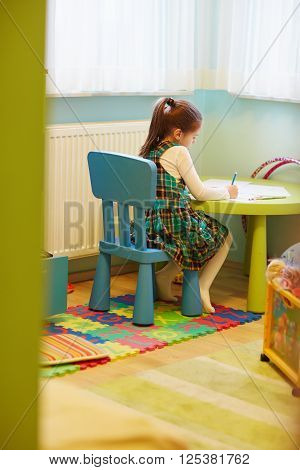 A little girl drawing quietly in her room