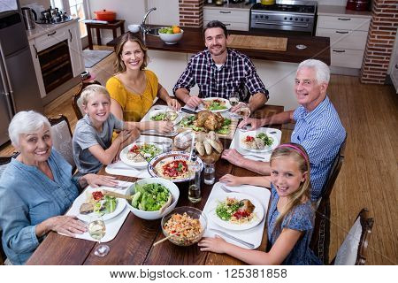 Portrait of multi-generation family having meal in kitchen at home