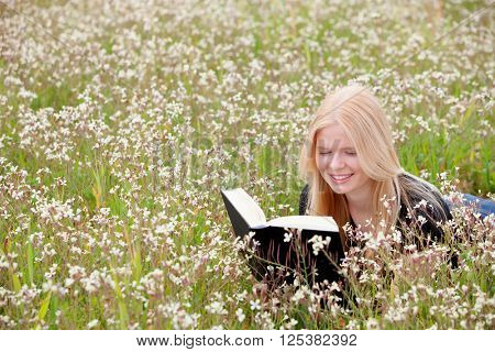 Relaxed young woman reading a book on nature