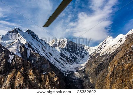 Aerial View of High Altitude Snowbound Mountains with Massive Glaciers Sharp Rock Ridges and Ice Slopes from Helicopter with Rotating Screw Blade