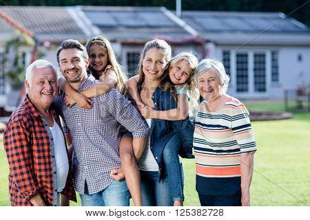 Portrait of happy multi-generation family standing together in the garden
