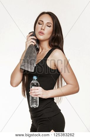 Portrait of good looking brunette woman in sports outfit. Fit woman at the gym tired after workout. Healthy lifestyle concept.