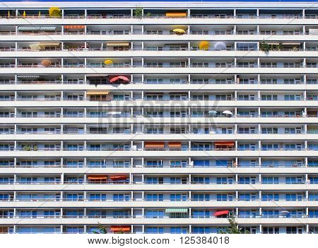 Wall of tall residential building, background of balconies with colorfull umbrellas and awnings.