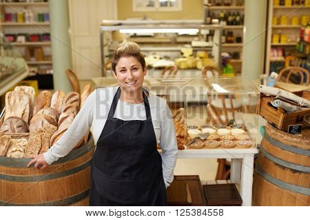 A young deli employee standing in front of the pastry display