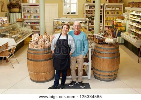 A father and daugther standing together in their deli