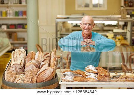 An elderly deli owner standing at the pastry display in his shop