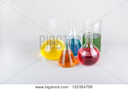 Different forms laboratory glassware with red green blue orange and yellow liquid on white background. Space for text
