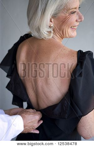 Man closing an old woman dress