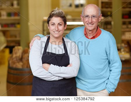 A deli owner and his daughter standing in their shop