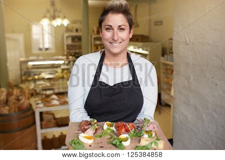 A female deli worker bringing you a snack plate