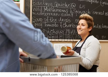 A female deli employee ringing up a young man's purchases
