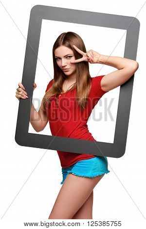 Beautiful bright girl standing looking through the frame and looking through hand V sign, over white background