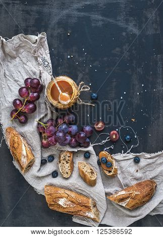 French baguette cut into pieces, red grapes, blueberry and salty caramel sauce on linen towel over rustic dark background with a copy space. Top view, vertical