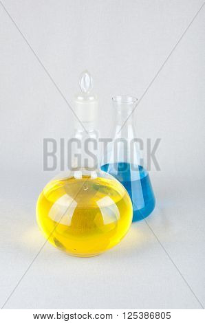 Two laboratory glassware and blue yellow liquid inside on white background. Vertical photo