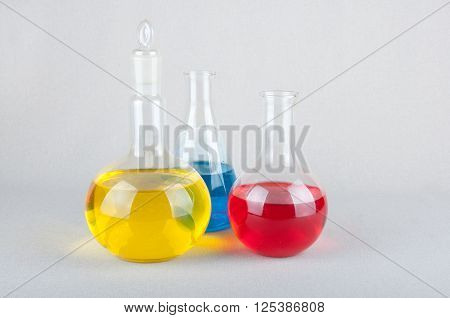 Three different forms laboratory glasswares and yellow blue red liquid inside on white background