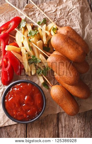Corn Dogs, French Fries, Pepper And Ketchup Close-up. Vertical Top View