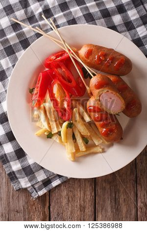 Fast Food: Corn Dog And Fries On A Plate Close-up. Vertical Top View