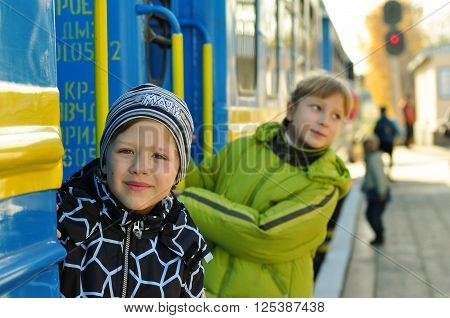 boy with the girl on the platform holding on to the railing of blue wagon