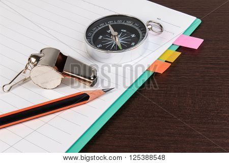 Metal Whistle, Pencil, Compass With Notebook On Dark Wooden Background.