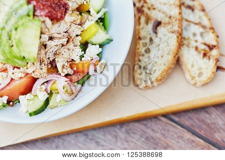 Cropped image of a colourful chicken salad with avocado, sundried tomatoes, yellow peppers, red onion, and feta with two slices of freshly baked bread alongside
