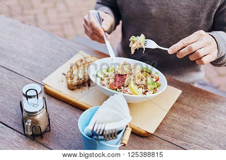 Cropped image of a man on his lunch break eating a fresh and healthy salad with chicken, avocado, sundried tomatoes and fresh sliced baguette on the side while sitting at a wooden table